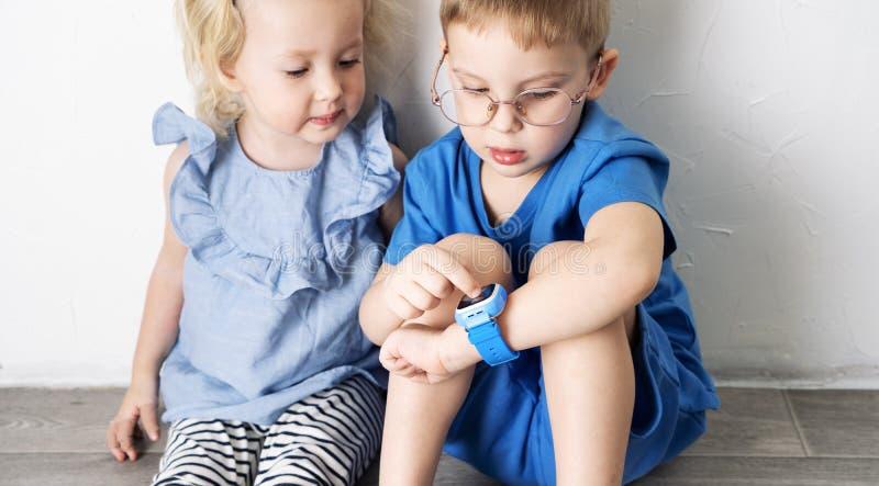 Un niño del niño pequeño en una camiseta azul y vidrios muestra a muchacha su reloj elegante y presiona un finger imagen de archivo