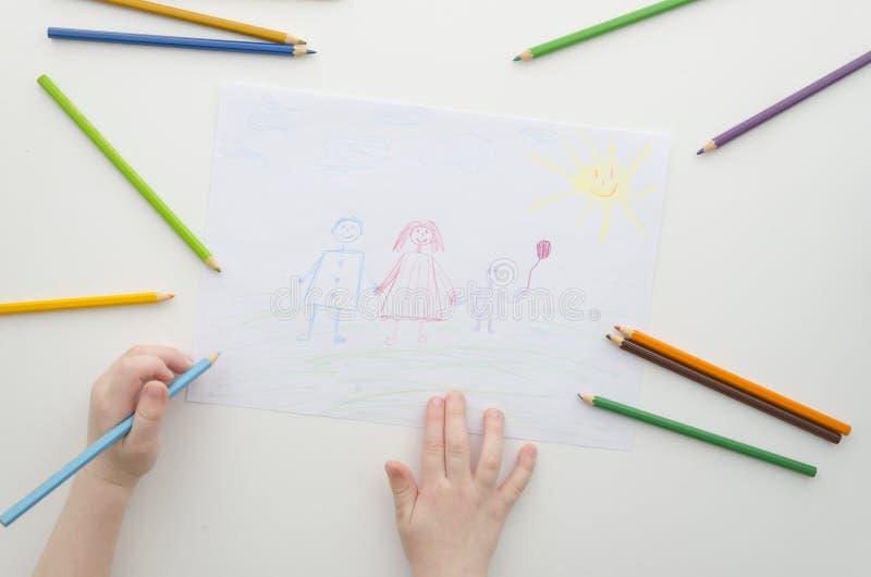 Un niño dibuja a su familia con los lápices El dibujo y los lápices coloreados del niño Dibujo de la familia en un Libro Blanco V imagenes de archivo