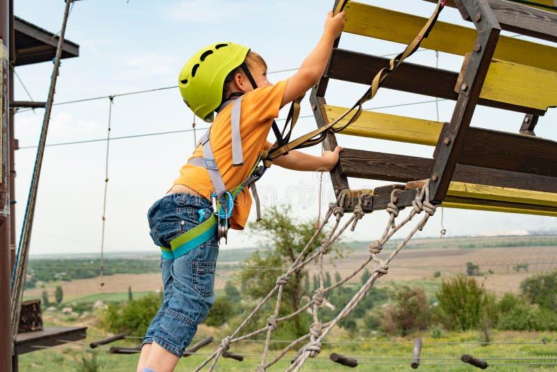 Un niño en el teleférico en un parque extremo Un muchacho vestido en un casco y un seguro protectores, supera obstáculos en el ca fotografía de archivo