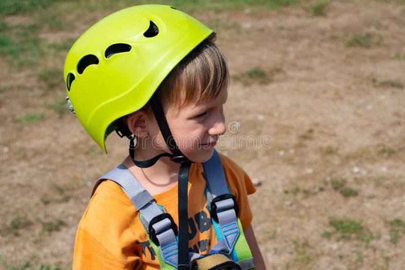 Un niño en el teleférico en un parque extremo Un muchacho vestido en un casco y un seguro protectores, supera obstáculos en el ca fotos de archivo