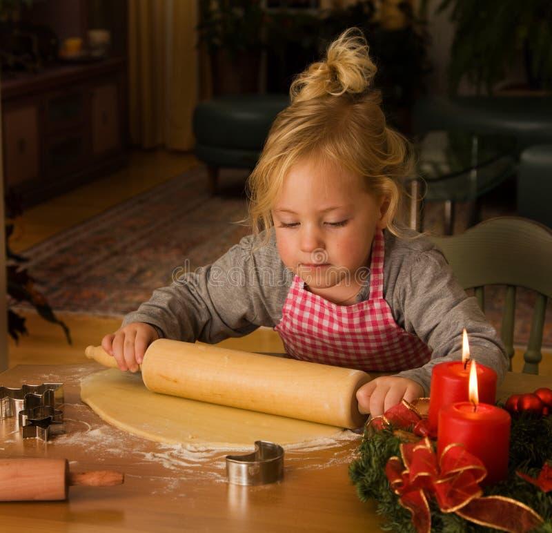 Un niño en la Navidad en advenimiento al cocer al horno las galletas fotos de archivo libres de regalías