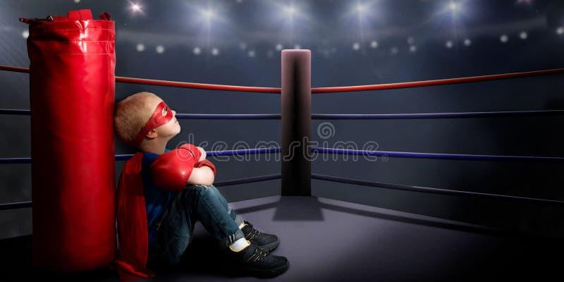 Un niño en un traje del super héroe se sienta en el anillo y los sueños de las victorias del boxeo fotografía de archivo libre de regalías