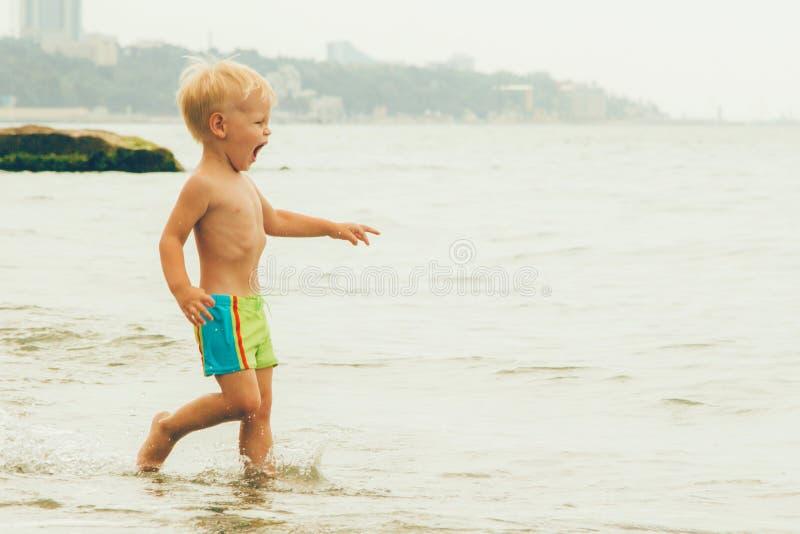 Un niño en troncos que nadan verdes con descensos de un punto fijo en el mar, fotos de archivo