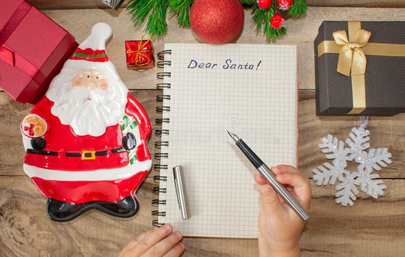 Un niño escribe una letra a Santa Claus, las manos de los niños con una pluma en un fondo de madera con las decoraciones y los re imagenes de archivo