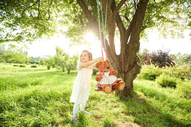Un niño está jugando con un oscilación imagen de archivo libre de regalías