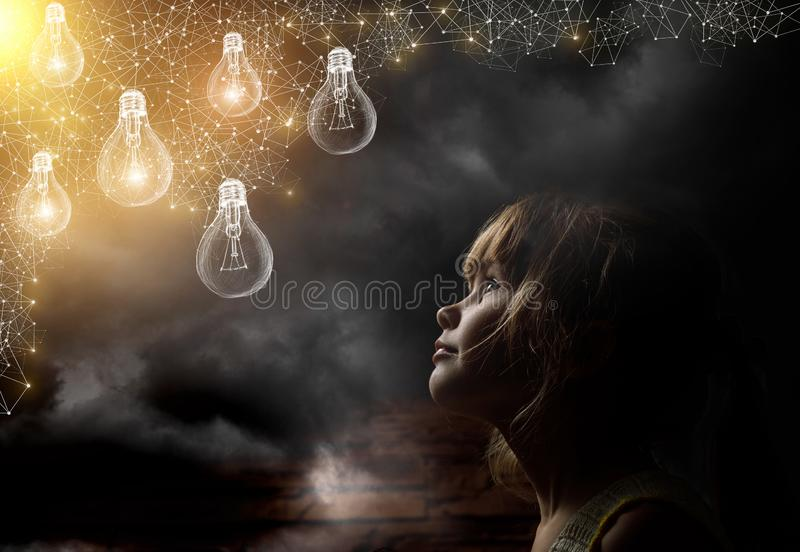 Un niño está mirando ardiendo bombillas pintadas imagen de archivo libre de regalías