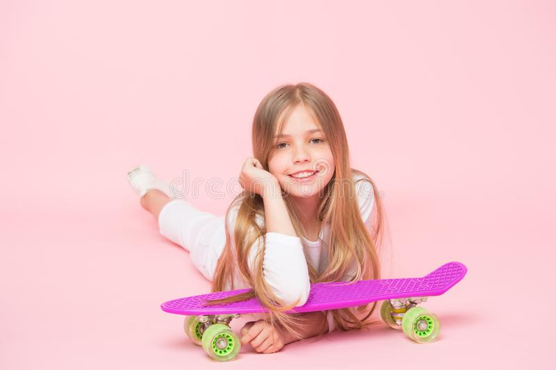 Un niño extremo Pequeño niño que se relaja en el monopatín en fondo rosado Pequeño niño lindo con el tablero violeta del penique fotos de archivo libres de regalías
