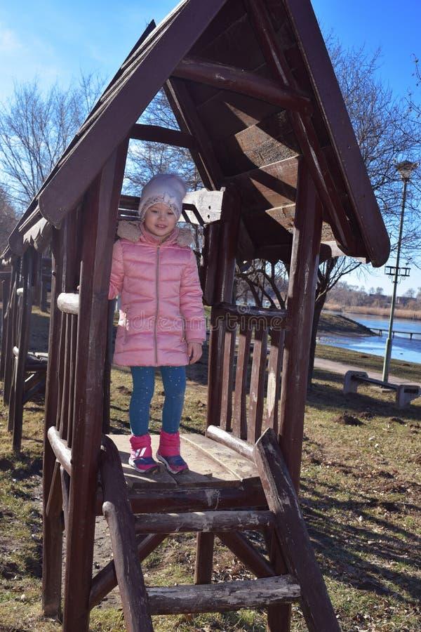Un niño feliz caucásico hermoso de la muchacha que ríe y que mira fuera de la casa de madera en el parque al aire libre 4 años de fotos de archivo