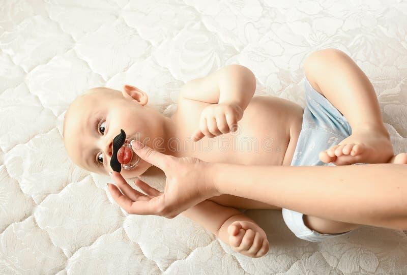 Un niño hermoso con un pacificador en la boca en forma de bigote emociones de bebé divertidas Higiene del cuidado del bebé fotos de archivo libres de regalías