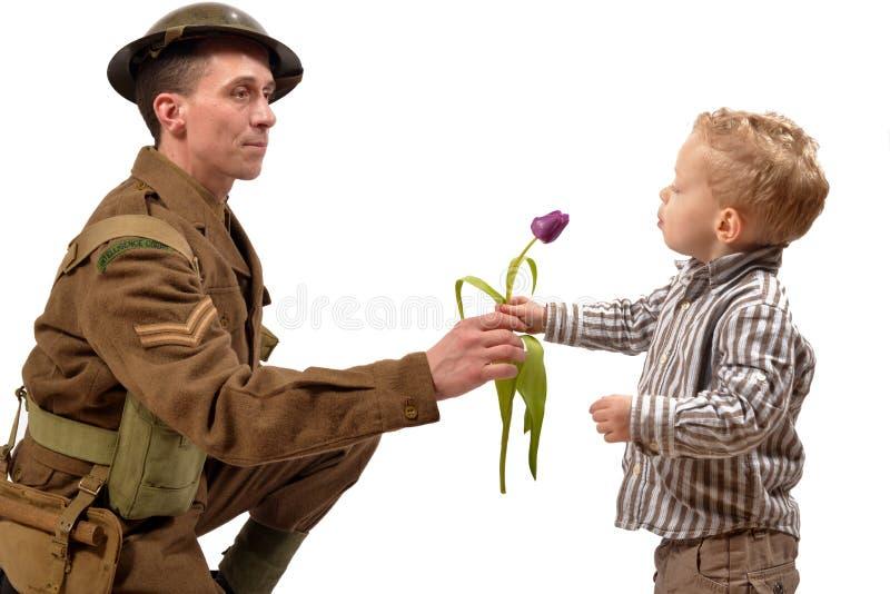 Un niño joven da una flor a un soldado británico fotos de archivo libres de regalías
