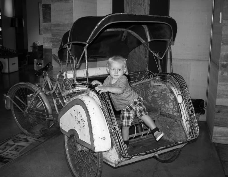 Un niño joven que se sienta en un coche viejo de la moda foto de archivo libre de regalías