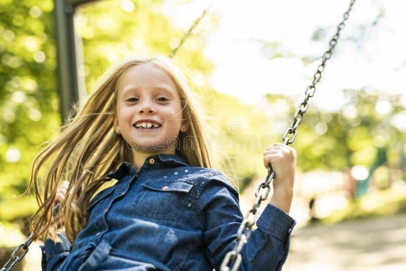 Un niño, jugando en la estación del otoño del patio fotos de archivo