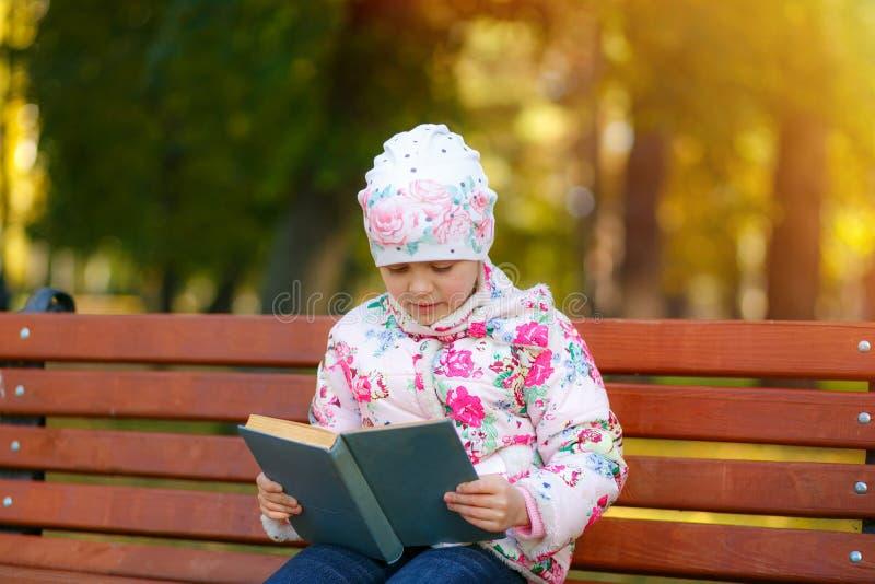 Un niño lindo está leyendo un libro en el parque fotos de archivo