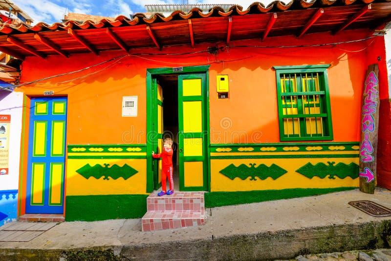 Un niño local delante de su casa en Guatapé fotografía de archivo