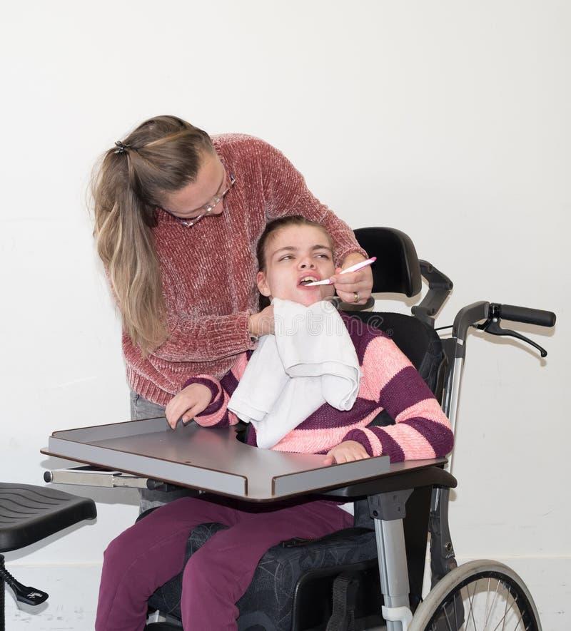 Un niño minusválido en una silla de ruedas así como un trabajador voluntario del cuidado foto de archivo