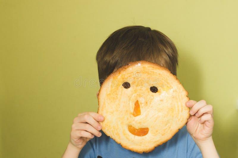 Un niño ocultado detrás de una galleta en forma de una taza con una sonrisa C fotografía de archivo