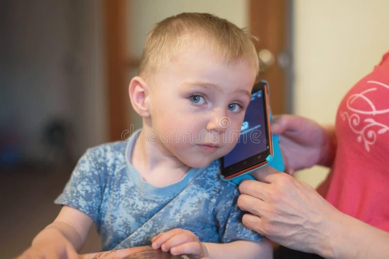 Un niño pequeño, 1,5 años, se sienta en el revestimiento del ` s de la mujer y escucha un teléfono móvil foto de archivo