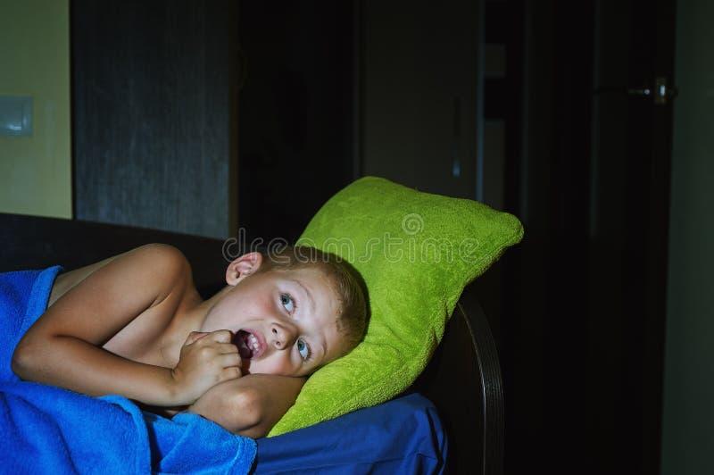 Un niño pequeño asustado asustado en cama en la noche, niñez teme foto de archivo