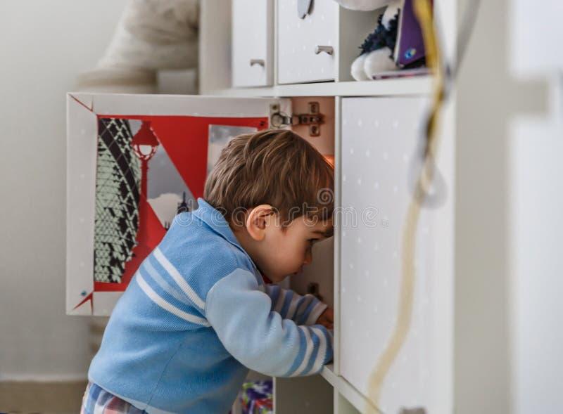 Un niño pequeño busca sus juguetes dentro de un armario imagenes de archivo