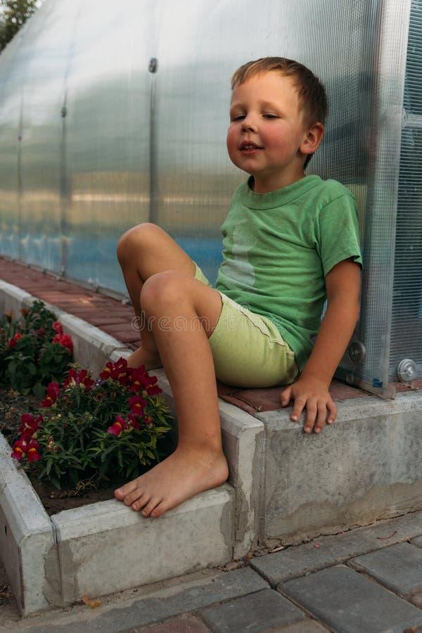 Un niño pequeño cansado se sienta en una trayectoria cerca de una cama descalzo niños del muchacho del granjero foto de archivo libre de regalías