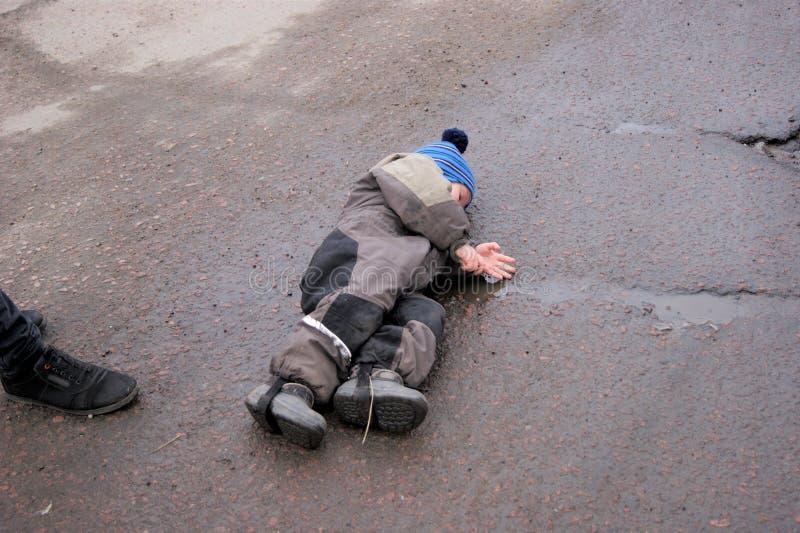 Un niño pequeño coloca en el asfalto para expresar su protesta y desacuerdo con el padre fotos de archivo