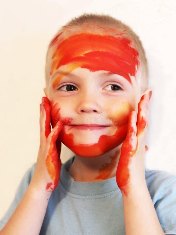 Un niño pequeño con la cara y las manos manchadas con las pinturas coloreadas foto de archivo