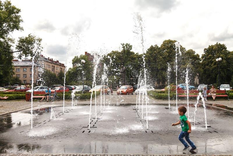 Un niño pequeño corre alrededor de la fuente en el cuadrado central de Uzhhorod el 13 de junio de 2018 imagen de archivo