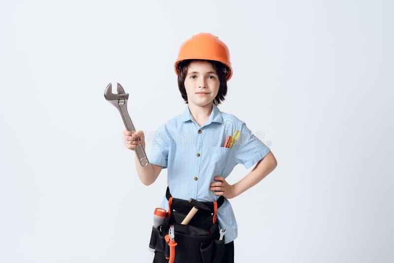 Un niño pequeño en forma y casco del reparador El muchacho detiene a una llave inglesa ajustable en su mano fotografía de archivo