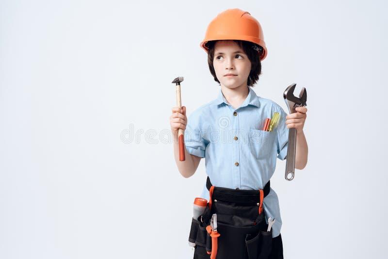 Un niño pequeño en forma y casco del reparador El muchacho sostiene una llave inglesa ajustable y un martillo en su mano fotos de archivo libres de regalías