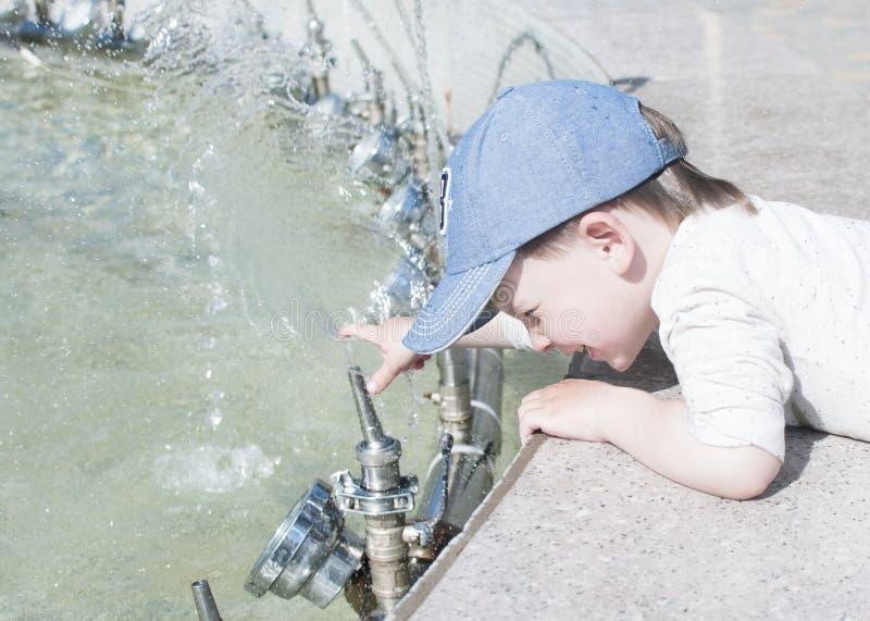 Un niño pequeño en la ciudad juega cerca de la fuente con agua fotografía de archivo libre de regalías