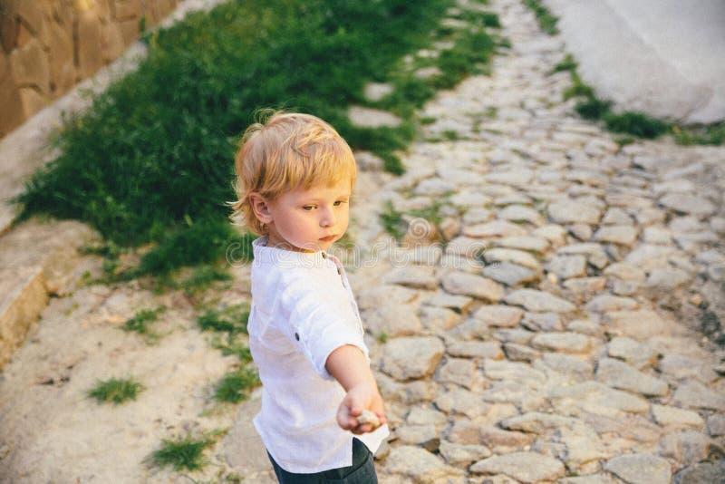 Un niño pequeño en la ropa blanca en el fondo de la piedra y de la hierba foto de archivo