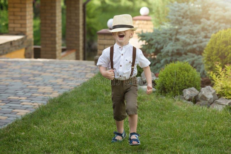 Un niño pequeño en un sombrero de paja camina en el parque imagen de archivo