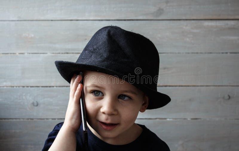 Un niño pequeño en un sombrero sostiene un teléfono fotos de archivo