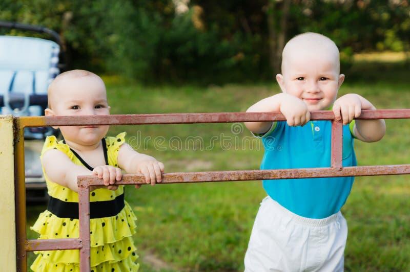 Un niño pequeño en una camisa azul y una muchacha en un vestido amarillo se están colocando detrás de una cerca del hierro imagen de archivo libre de regalías