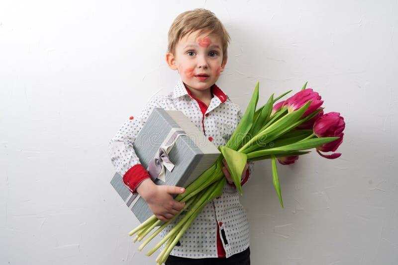 Un niño pequeño en una camisa elegante e impresiones de besos en su cara está sosteniendo un ramo de tulipanes y de una caja con  imagenes de archivo