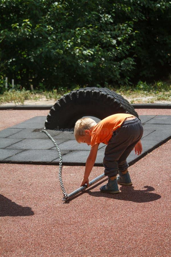 Un niño pequeño en una camiseta anaranjada está intentando levantar a un instructor pesado en la calle imagenes de archivo