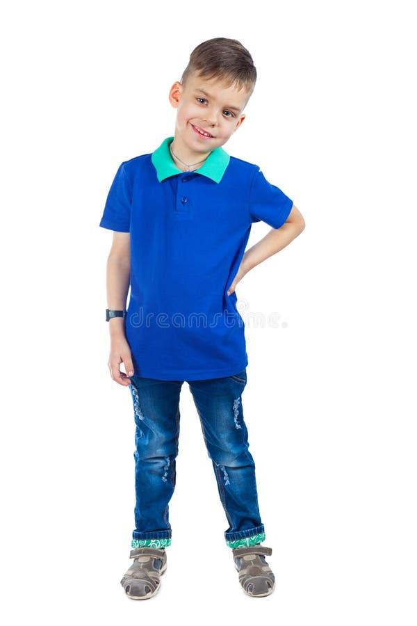 Un niño pequeño en una camiseta azul es sonriente y de mirada de la leva foto de archivo libre de regalías