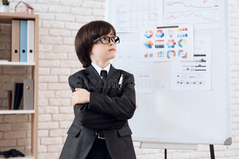 Un niño pequeño en vidrios y traje se presenta como hombre de negocios El muchacho oscuro-cabelludo juega a un hombre rico imagenes de archivo