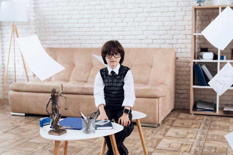 Un niño pequeño en vidrios y traje se presenta como hombre de negocios El muchacho oscuro-cabelludo juega a un hombre rico fotos de archivo