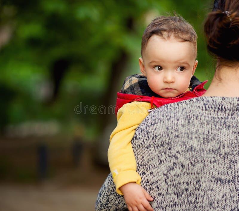 Un niño pequeño encantador mira sobre el hombro de su madre fotografía de archivo libre de regalías