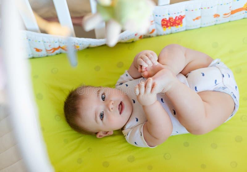 Un niño pequeño encantador que miente en cama y que se sostiene entrega su le imagen de archivo