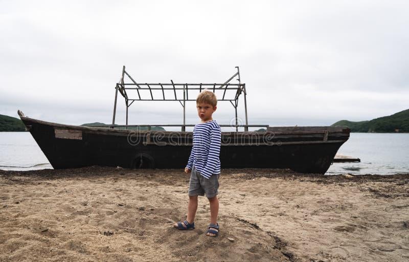 Un niño pequeño es el hijo de un pescador en una situación rayada del chaleco en la orilla arenosa del mar contra el contexto de fotos de archivo