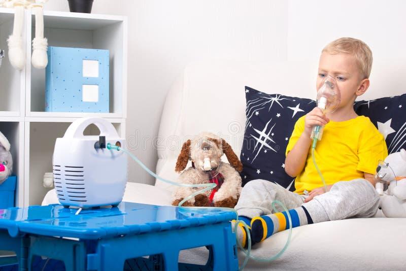 Un niño pequeño hace la inhalación con un nebulizador Un tratamiento casero Un niño y un perro de juguete en máscaras fotografía de archivo