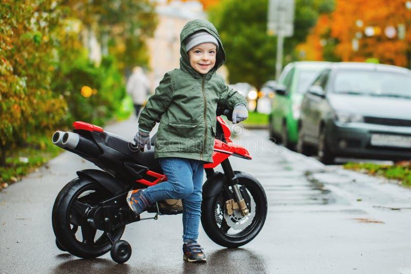 Un niño pequeño hermoso que presenta en su motocicleta del rojo del ` s de los niños El concepto de niños de enseñanza a los vehí fotos de archivo