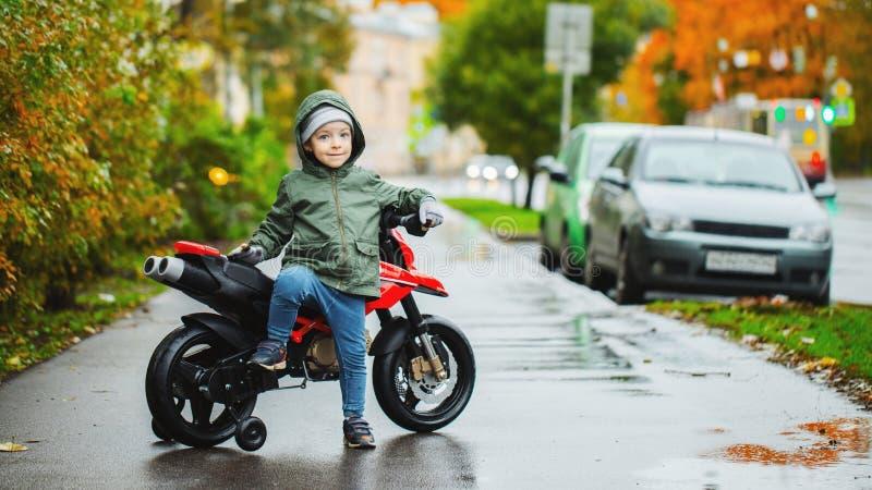 Un niño pequeño hermoso que presenta en su motocicleta del rojo del ` s de los niños El concepto de niños de enseñanza a los vehí imágenes de archivo libres de regalías