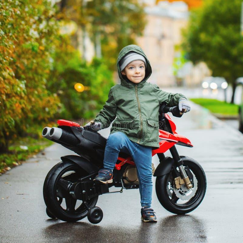 Un niño pequeño hermoso que presenta en su motocicleta del rojo del ` s de los niños El concepto de niños de enseñanza a los vehí imagen de archivo libre de regalías