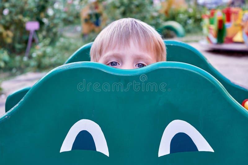 Un niño pequeño mira hacia fuera de detrás el juguete de un niño bajo la forma de rana fotos de archivo