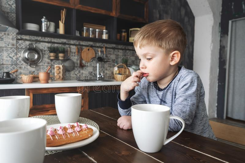 Un niño pequeño pensativo se sienta en una tabla con un té y tortas del circley Lamedura de su finger Retrato imagenes de archivo