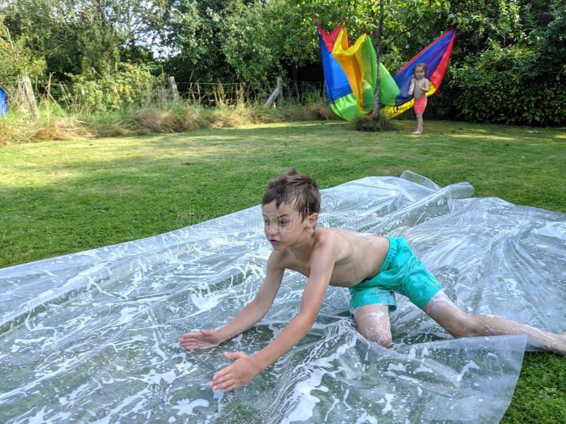 Un niño pequeño que desliza abajo un resbalón y una diapositiva imágenes de archivo libres de regalías