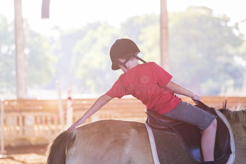 Un niño pequeño que monta un caballo Primeras lecciones de la equitación imagenes de archivo